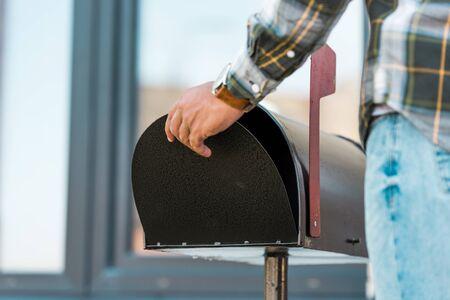 cropped view of man opening black mailbox Reklamní fotografie