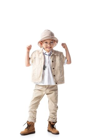 full length view of smiling explorer boy looking at camera and showing yes gesture isolated on white