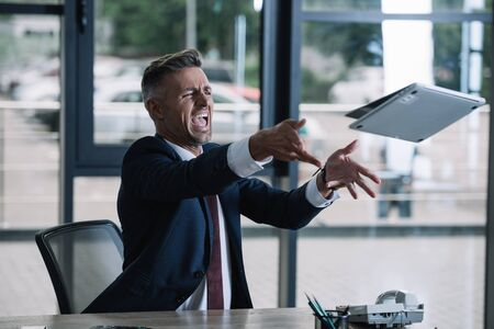 angry businessman throwing in air laptop in office