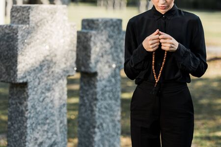 cropped view of woman holding rosary beads near tombstones