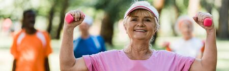 panoramic shot of cheerful senior woman in cap holding dumbbells while exercising near pensioners Foto de archivo - 130213105