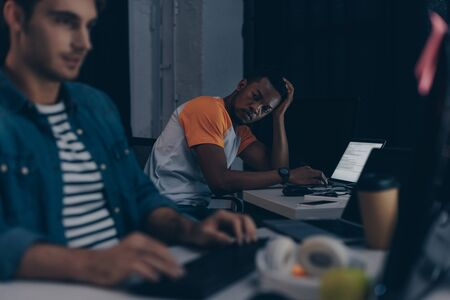 selective focus of african american programmer looking at multicultural colleague while working together at night in office Stock Photo