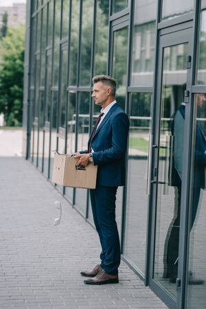 side view of fired man in suit standing near building with retro phone in carton box