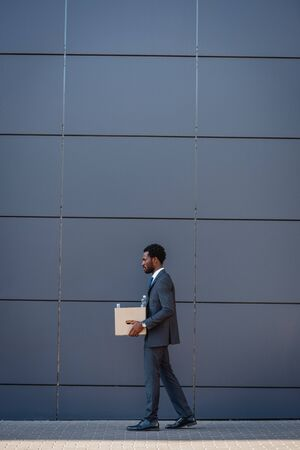 side view of fired african american businessman carrying carton box while walking along wall Foto de archivo