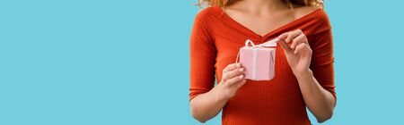 cropped view of young woman holding gift box isolated on blue