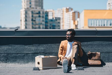fired african american businessman sitting on rooftop near carton box