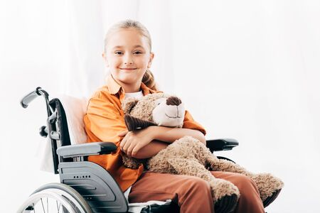 smiling kid holding teddy bear and sitting on wheelchair