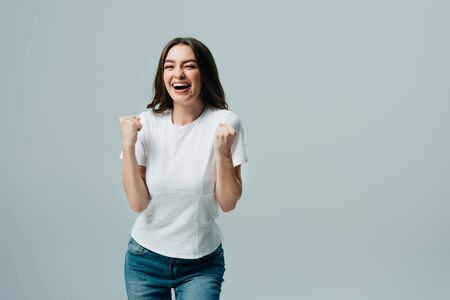 excited happy beautiful girl in white t-shirt showing yes gesture isolated on grey