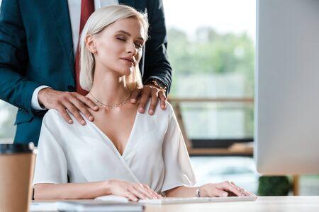 przycięty widok biznesmena w garniturze dotykającego atrakcyjnej blondynki z zamkniętymi oczami