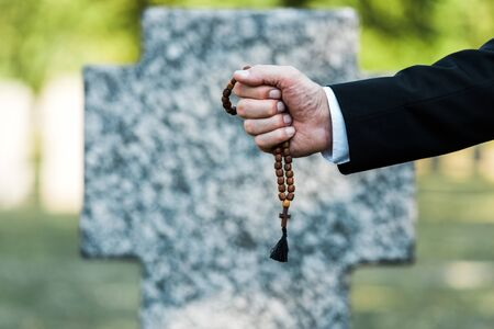 cropped view of elderly man holding rosary beads near gravestone
