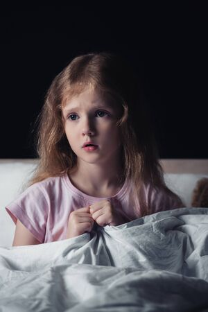 frightened kid looking away while sitting on bedding isolated on black