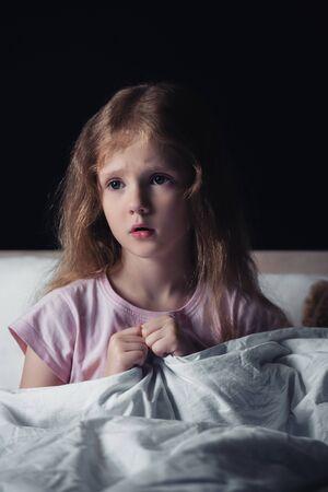 verängstigtes Kind, das wegschaut, während es auf der Bettwäsche sitzt, isoliert auf schwarz Standard-Bild