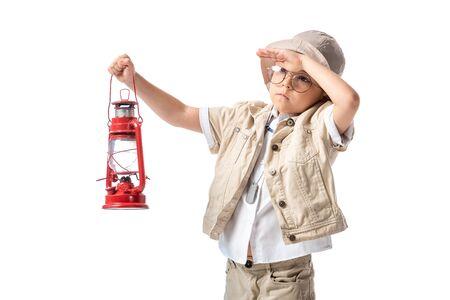 esploratore pensieroso ragazzo in occhiali e cappello che tiene lanterna rossa e guarda a distanza isolato su bianco