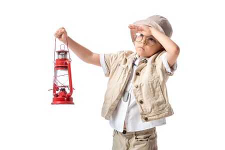 pensive explorer boy in glasses and hat holding red lantern and looking at distance isolated on white