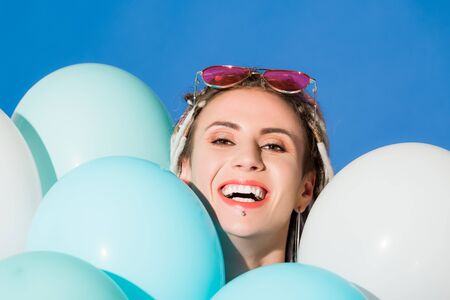 beautiful smiling girl posing with balloons isolated on blue Фото со стока