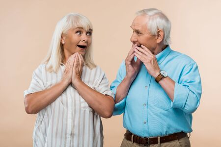 surprised senior woman looking at husband covering face with hands isolated on beige