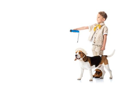 full length view of explorer child holding flashlight and beagle dog in hat on white