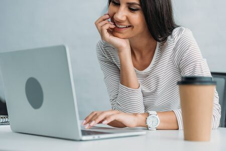 attractive and brunette woman smiling and using laptop in apartment