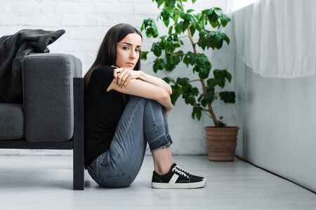 depressed young woman sitting on floor at home and looking at camera