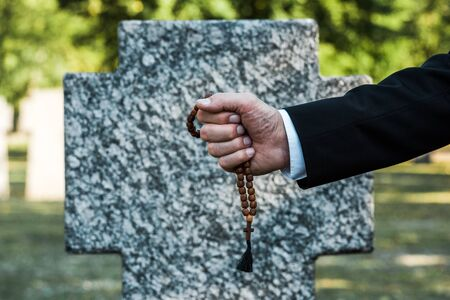 cropped view of man holding rosary beads near gravestone Фото со стока