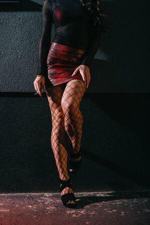 Ausgeschnittene Ansicht einer Frau im roten Rock, die mit Zigarette in der Nähe einer Wand steht