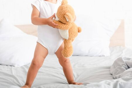 Cute barefoot child in white clothes standing on bed with his brown toy bear Stock Photo