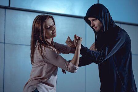 belle femme se battre avec un voleur dans le passage souterrain