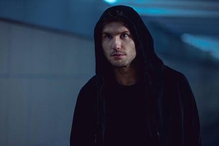 handsome thief in black hoodie in underpass Stock Photo