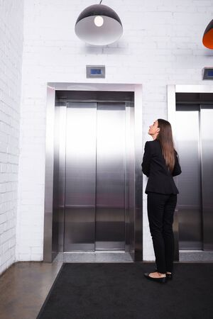 back view of businesswoman in formal wear standing in lobby and waiting for elevator
