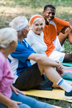 selective focus of cheerful multicultural men and women in sportswear sitting on fitness mats Foto de archivo - 130218040