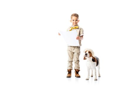 full length view of smiling explorer kid holding placard and beagle dog in hat isolated on white Reklamní fotografie