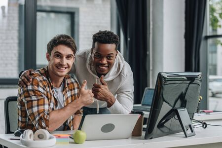 two young multicultural programmers smiling at camera and showing thumbs up