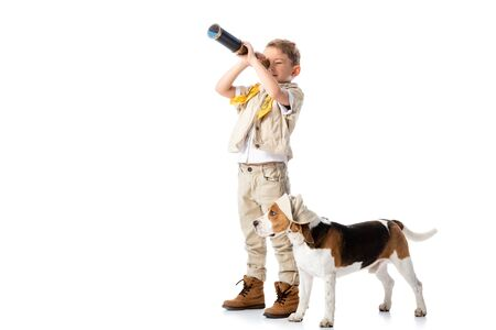 full length view of preschooler explorer boy with beagle dog looking in spyglass isolated on white
