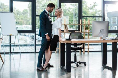 Gut aussehender Geschäftsmann, der eine attraktive junge Frau berührt, während er im Büro flirtet