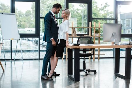 handsome businessman touching attractive young woman while flirting in office