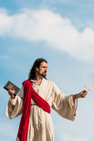 jesus holding holy bible and wooden cross against blue sky with clouds Foto de archivo