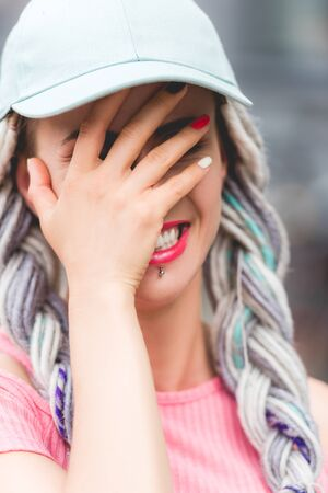girl with dreadlocks in hat laughing and covering face