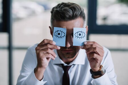 businessman in suit holding sticky notes with drawn eyes near face