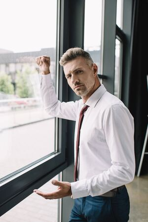 displeased businessman in suit standing near windows with clenched fist Фото со стока