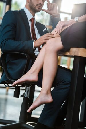 cropped view of man touching leg of woman sitting on table in office