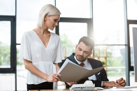 selective focus of attractive businesswoman holding folder near businessman in office