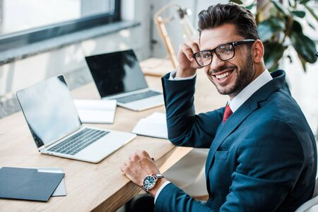 selective focus of cheerful man in glasses looking at camera near laptops with blank screens Фото со стока