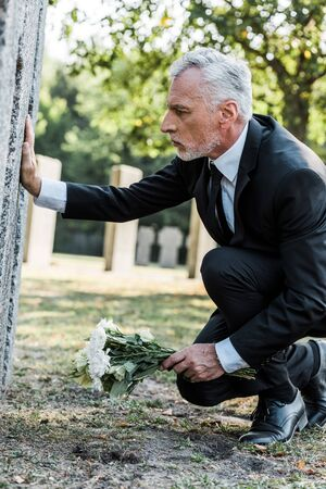upset man with grey hair putting flowers near tomb in cemetery