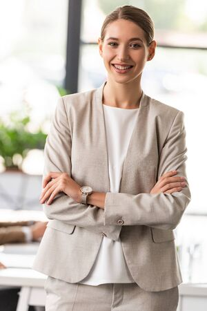 front view of confident businesswoman in formal wear standing with crossed arms in office