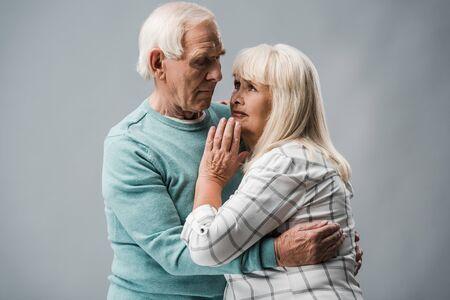 senior man with grey hair hugging upset wife on grey