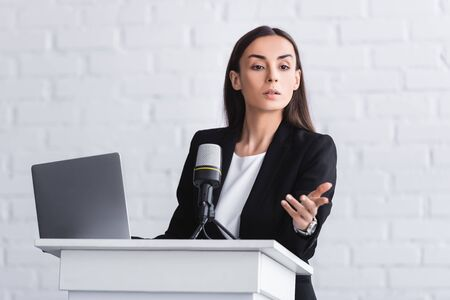 attractive serious lecturer gesturing while speaking from podium tribune