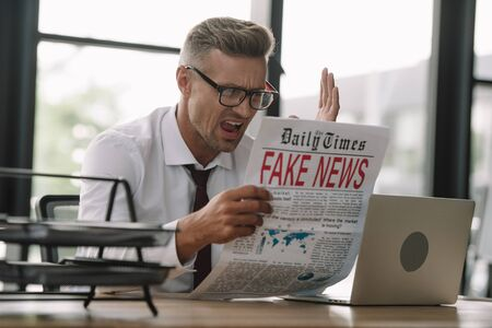selective focus of emotional businessman in glasses gesturing while reading newspaper with fake news Фото со стока