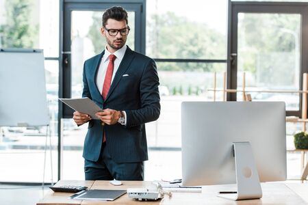 serious businessman holding folder and looking at wooden desk in office