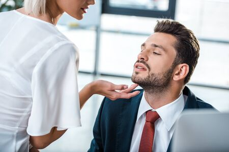 cropped view of woman touching face of handsome bearded man with closed eyes