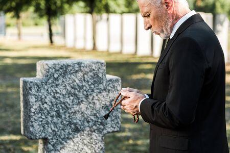 man with grey hair looking at rosary beads near tombstone Фото со стока